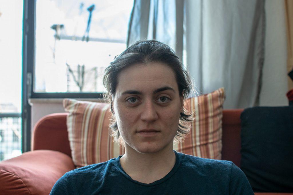 Vanessa sitzt vor ihrem Sofa.