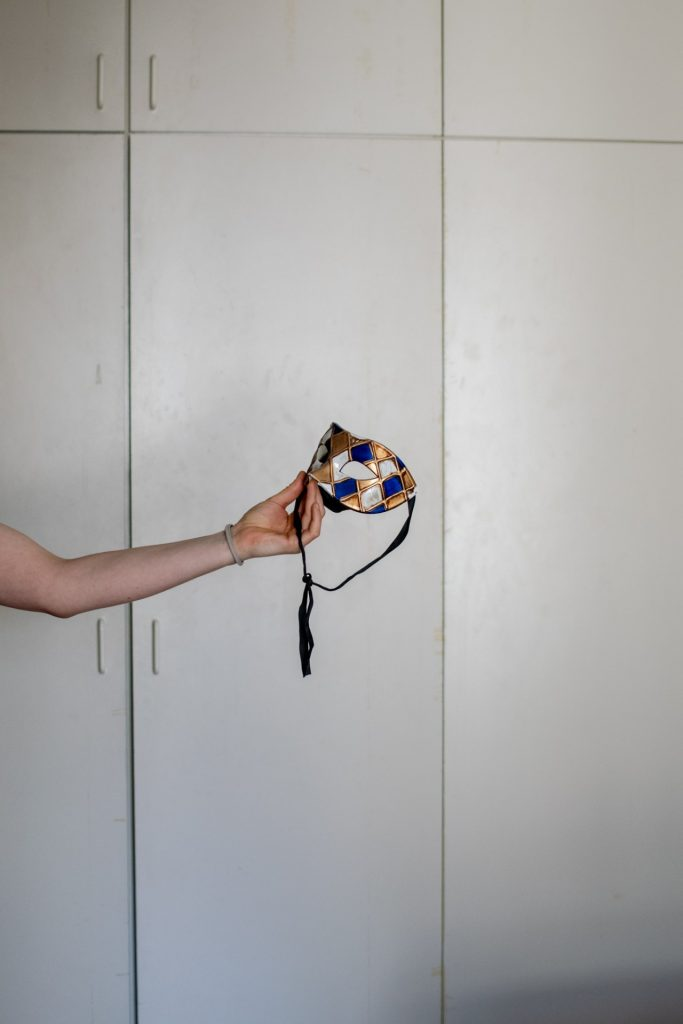 Eine Maske ist in der Bildmitte zu sehen. Vanessa hält sie hinein.