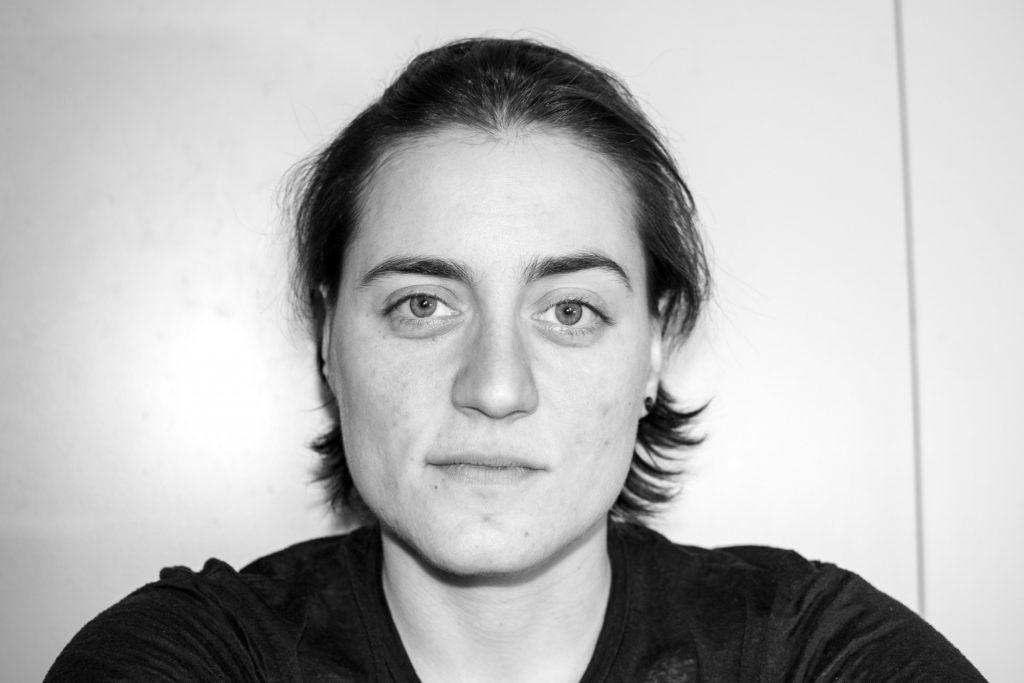 Vanessa sitzt vor einer Wand und lächelt und die Kamera. In schwarz-weiß.