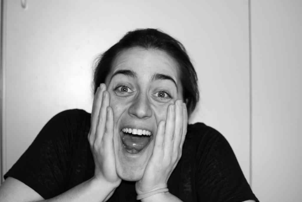 Vanessa freut sich. Sie hat den Mund geöffnet und schlägt die Hände an die Wangen. Das Foto ist in schwarz-weiß.