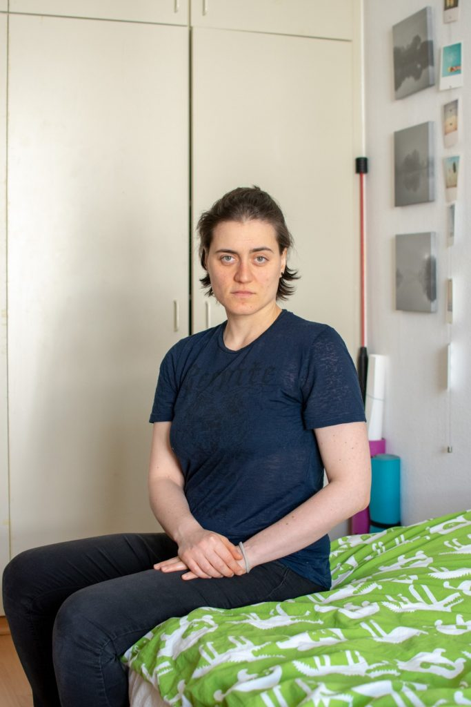 Vanessa blickt sitzend von ihrem Bett in die Kamera.