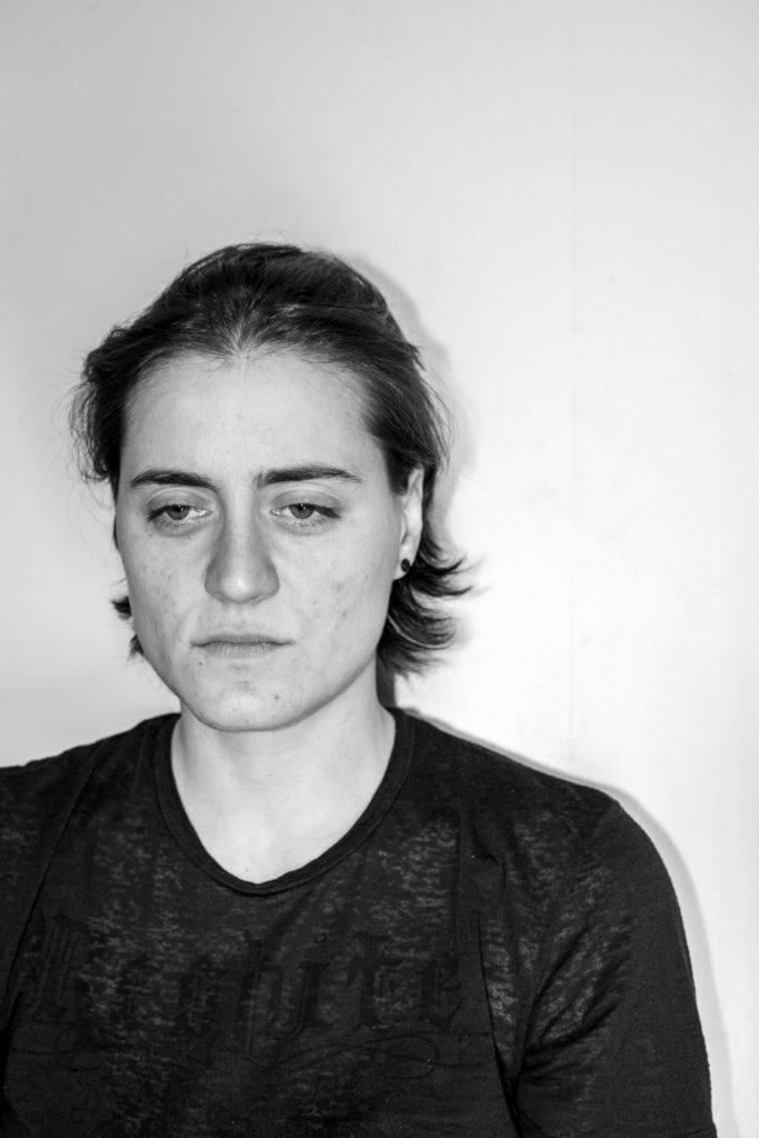 Vanessa sitzt vor einer Wand und sieht traurig aus in Schwarz-Weiß